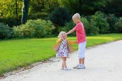 Brother y hermana que juegan en parque del otoño Fotos de archivo libres de regalías