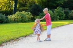 Brother y hermana que juegan en parque del otoño Imagenes de archivo