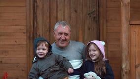 Brother y hermana que se sientan en las rodillas de abuelo El viejo hombre abraza el nieto y a la nieta Abuelo del beso de la muc Imagenes de archivo