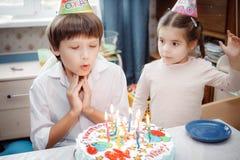 Brother y hermana que sientan en casa la torta con las velas fotos de archivo libres de regalías