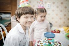 Brother y hermana que sientan en casa la torta con las velas imagen de archivo