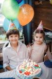 Brother y hermana que sientan en casa la torta con las velas fotografía de archivo libre de regalías