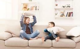 Brother y hermana que tienen lucha de almohada en el sofá fotografía de archivo