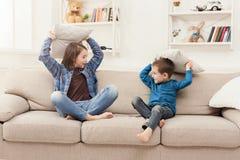 Brother y hermana que tienen lucha de almohada en el sofá foto de archivo libre de regalías