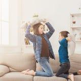 Brother y hermana que tienen lucha de almohada en el sofá imagen de archivo