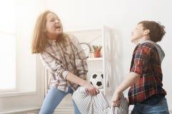 Brother y hermana que tienen lucha de almohada en el sofá en casa imágenes de archivo libres de regalías