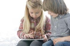 Brother y hermana que usa la tableta en dormitorio Imagenes de archivo