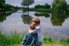 Brother y la hermana está cerca de una charca Dos niños que se colocan en la hierba alta cerca de una charca imagen de archivo libre de regalías