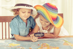 Brother y la hermana están considerando un mapa del mundo con magnificar Fotografía de archivo libre de regalías