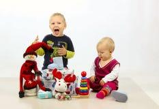 Brother y la hermana están jugando con los juguetes de la Navidad imagenes de archivo