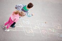 Brother y la hermana juegan a la rayuela Foto de archivo libre de regalías