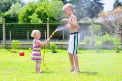Brother y la hermana que juegan con agua riegan en el jardín Imagenes de archivo