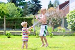 Brother y la hermana que juegan con agua riegan en el jardín Fotografía de archivo