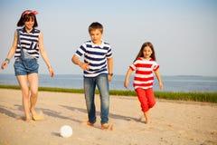 Brother y las hermanas juegan con una pelota de playa al aire libre Fotos de archivo libres de regalías