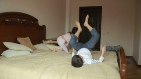 Brother y las luchas de la hermana y se empuja en casa en el dormitorio del ` de los padres el luchar para el teléfono almacen de video