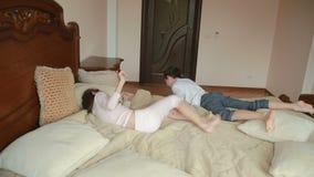 Brother y las luchas de la hermana y se empuja en casa en el dormitorio del ` de los padres el luchar para el teléfono metrajes
