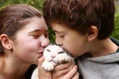 Brother y pares de los hermanos de la hermana con el gato Imagen de archivo