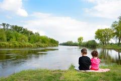 Brother y pequeña hermana que se sientan en el banco del río Imagenes de archivo