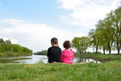 Brother y pequeña hermana que se sientan en el banco del río Imagen de archivo libre de regalías