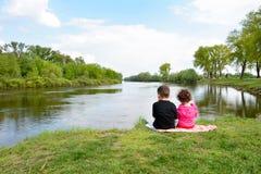 Brother y pequeña hermana que se sientan en el banco del río Fotos de archivo
