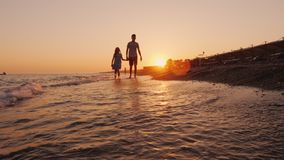 Brother y una hermana más joven que caminan a lo largo de la costa en la puesta del sol almacen de metraje de vídeo