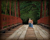 Brotherly love. Brothers walking across red bridge Royalty Free Stock Image