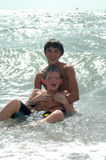 Brothers. Two brothers hang together in the ocean waves on vacation. Spending time with family. Happy Boys royalty free stock photo