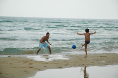 Brothers. Playing soccer on the beach Royalty Free Stock Photos