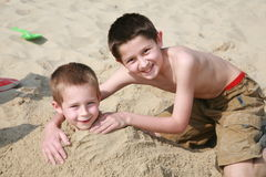 Brothers. Two young boys playing in the sand, the older one having buried his younger brother up to his neck in the sand Royalty Free Stock Photography