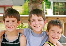 Brothers. Three Brothers With Arms Around Each Other Smiling royalty free stock photo