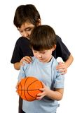 Brothers and basketball. Two brothers sharing a basketball, shot against white background Stock Images