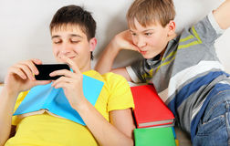 Brothers with a Books and Cellphone Stock Images