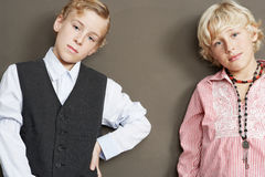 Brothers on Brown Background. Two young brothers standing together showing attitude and different personalities Royalty Free Stock Image