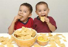 Brothers, Chips, and Queso 6. Two preschool brothers enjoy a huge bowl of tortilla chips and some queso stock image