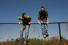 Brothers climing a fence Royalty Free Stock Photography