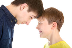 Brothers Conflict. Teenager and Kid looking to each other on the White Background closeup Stock Images