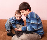 Brothers discovering a laptop Stock Photography