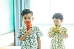 Brothers are drinking water on the bed  in the morning stock image