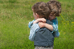 Brothers embrace. Three year old identical twins are in a meadow. They are dressed in shirts and vests of different colors and pattern. They passionately embrace Royalty Free Stock Image