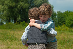 Brothers embrace. Three year old identical twins are in a meadow with trees. They are dressed in shirts and vests of different colors and pattern. They hug. One Stock Photo
