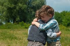 Brothers embrace. Three year old identical twins are in a meadow with trees. They are dressed in shirts and vests of different colors and pattern. They hug. One Stock Photos
