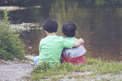 Brothers. Embraced watching the river Royalty Free Stock Images