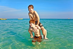 Brothers   enjoy the clear warm. Brothers are enjoying the clear warm water at the beautiful beach and playing pickaback Royalty Free Stock Photos
