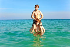 Brothers   enjoy the clear warm. Brothers are enjoying the clear warm water at the beautiful beach and playing pickaback Royalty Free Stock Photo