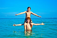 Brothers   enjoy the clear warm. Brothers are enjoying the clear warm water at the beautiful beach and playing pickaback Royalty Free Stock Images