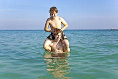 Brothers enjoy the clear warm water. Brothers are enjoying the clear warm water at the beautiful beach and playing pickaback Royalty Free Stock Image