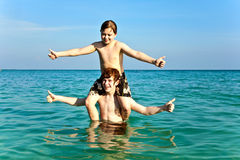 Brothers are enjoying the clear. Warm water at the beautiful beach and playing pickaback Stock Photos