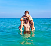 Brothers are enjoying the clear. Warm water at the beautiful beach and playing pickaback Royalty Free Stock Photography