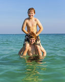 Brothers are enjoying the clear warm water in the ocean and play. Brothers are enjoying the clear warm water at the beautiful beach and playing pickaback Stock Photo