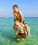 Brothers are enjoying the clear warm water in the ocean and play. Brothers are enjoying the clear warm water at the beautiful beach and playing pickaback Stock Photography